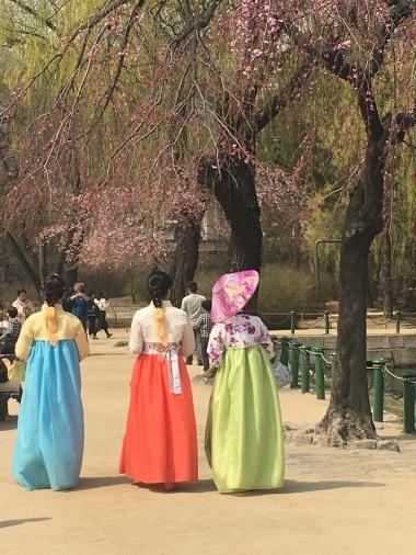 women in hanbok strolling the grounds.