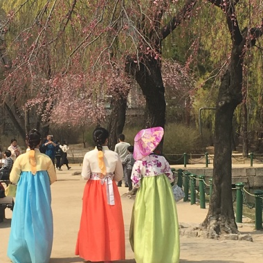 women in hanbok strolling the grounds.